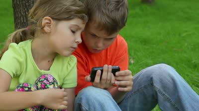 stock-footage-sister-watches-how-her-brother-plays-with-digital-game-on-cell-phone-when-kids-sit-together-at